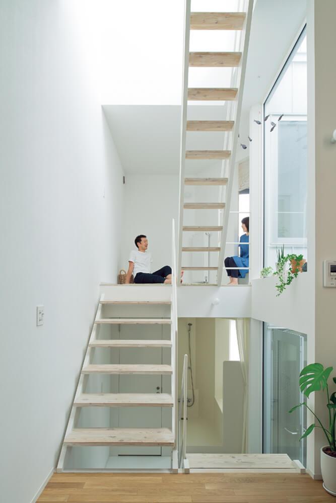 階段の踊り場が部屋になっているスキップフロアの住まい。左の壁から階段の右にある大開口までの距離はなんと2mしかないが、奥行きと高さのある空間構成で開放的に感じられる。大開口の外は太陽の光と風を室内に届ける光井戸で、外観からは想像がつかないほど室内は明るい