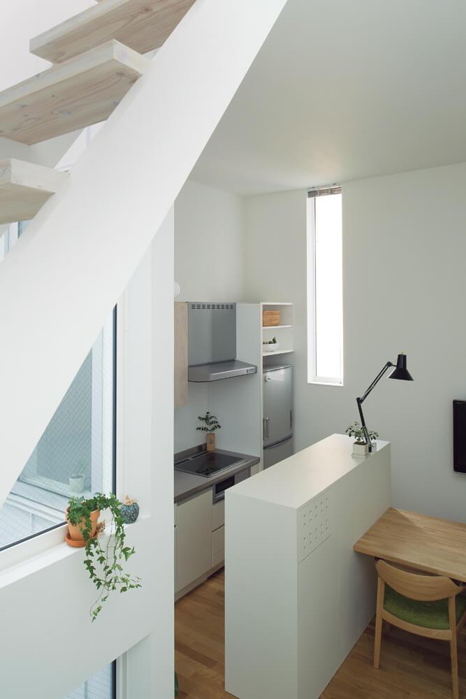 建物の奥、西側に位置するダイニング・キッチン。奥に見える窓は敷地裏の建物をかわす位置にレイアウト。キッチン背面の収納カウンターやダイニングテーブルは、部屋のサイズに合わせて造作