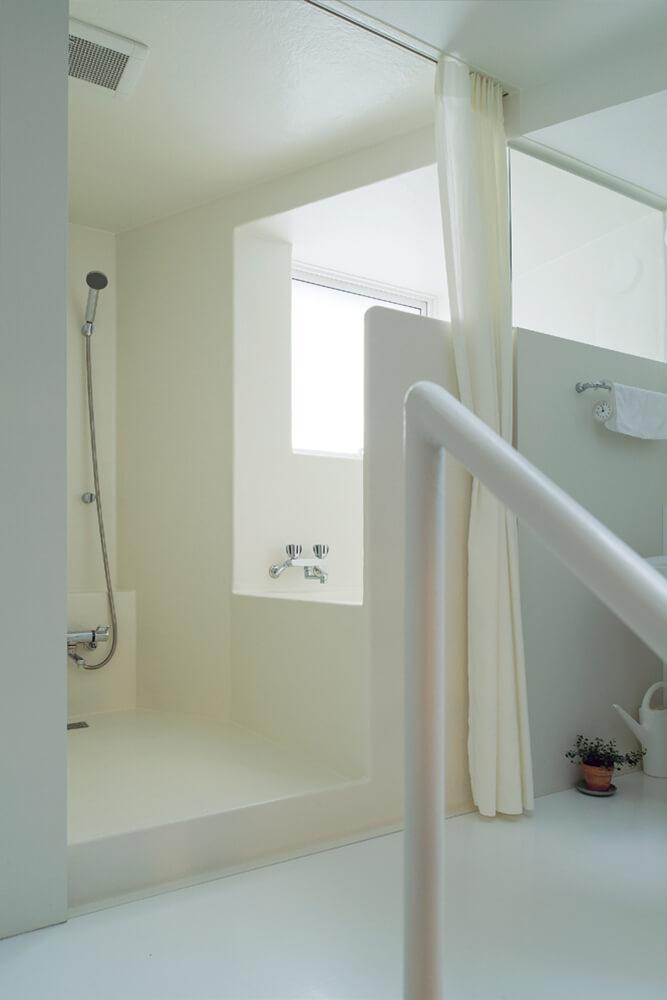 バスルーム。使用する時はカーテンを引き、普段は開けて空間をより広く見せている。右手には洗面化粧台があり、浴室利用時はカーテンを引いて脱衣スペースとして利用する
