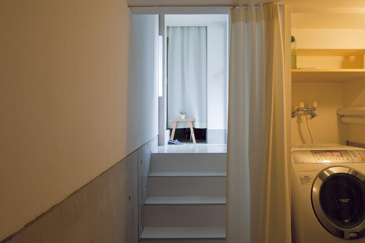 玄関から下がった半地下スペースは、洗濯室とクローゼット。階段下を利用して洗濯機を置き、背面のクローゼット部分に干し、そのまま収納。換気設備も設けている