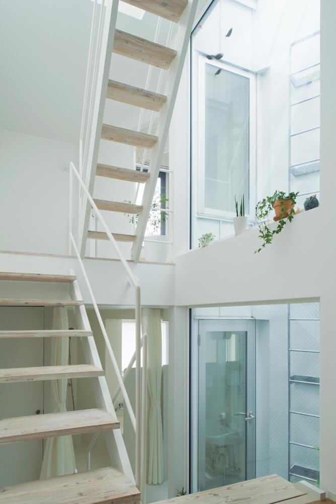内装は空間を広く明るく見せる効果のある白を基調に。オープンな階段に光井戸を隣接させることで室内全体に光がまわり、視界も広がる