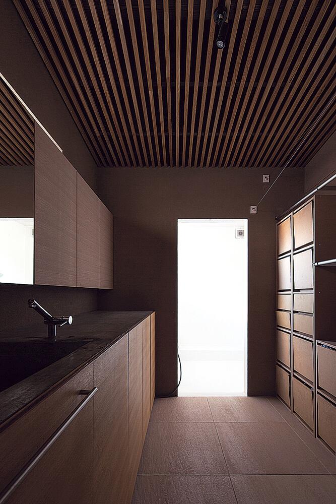 家事動線に配慮し、キッチンのすぐ隣に水まわりを配置。造作棚や内装はLDKと統一感を持たせたデザインに