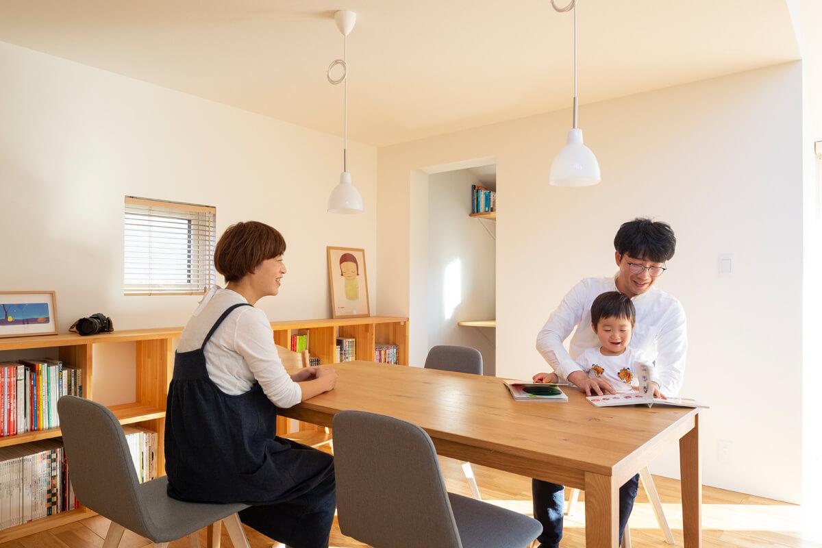 ダイニングは天井高を抑えて、落ち着いた空間に。木調の家具と白の内装で調和の取れたインテリア
