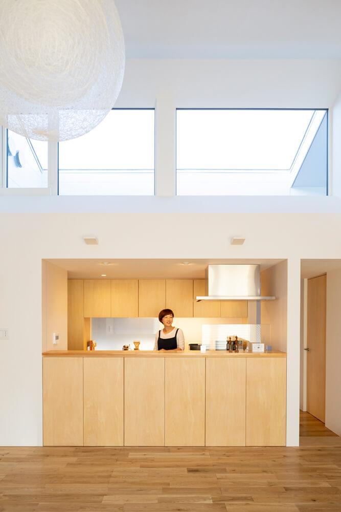 建物の中心に位置するキッチン。背後の壁は半透明のガラスをはめ込み、子ども部屋の気配が感じられるようにプランされている