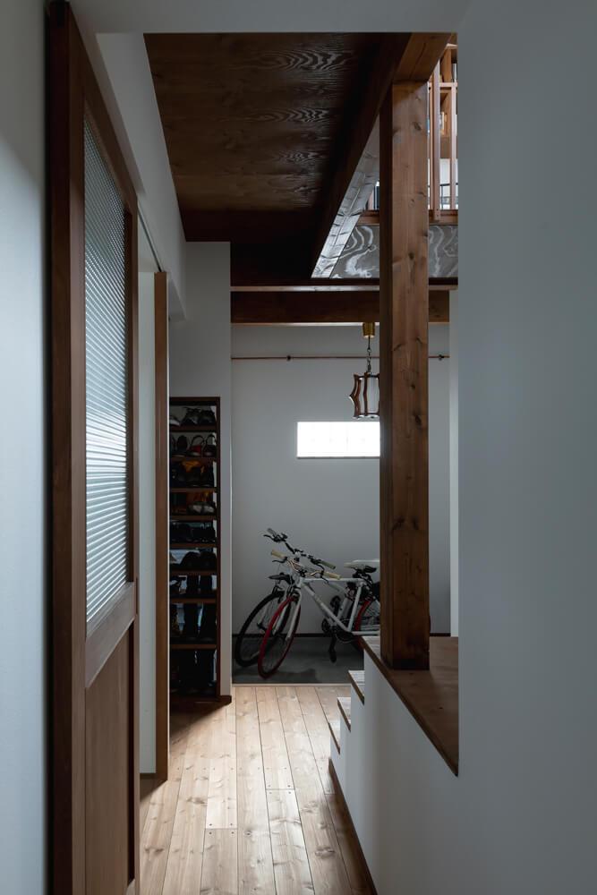 階段上部の吹き抜けとガラスブロックを入れた玄関の窓からの光で明るい玄関まわり