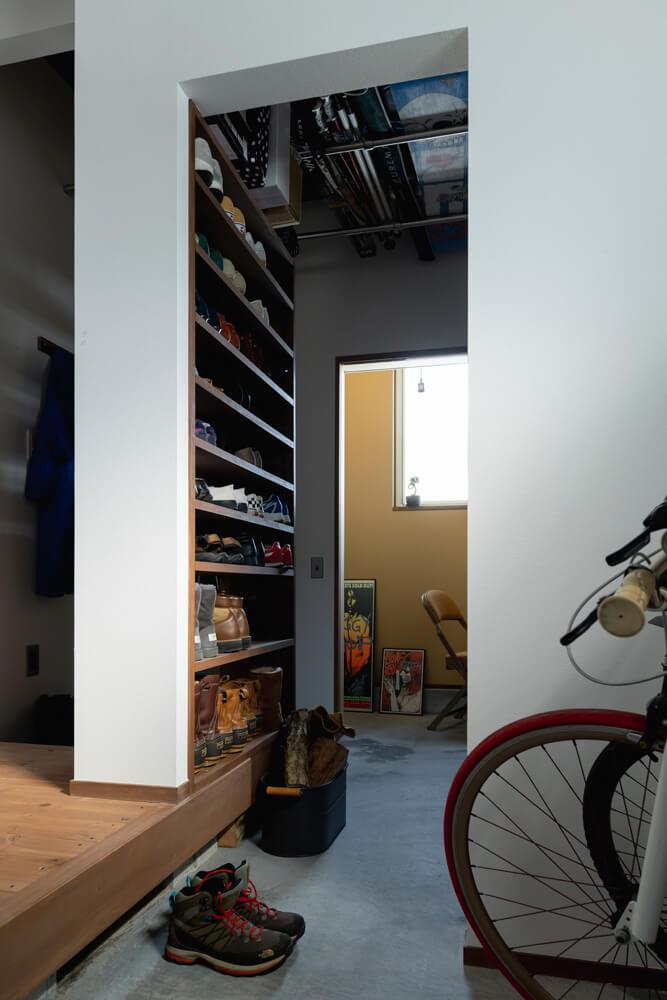 土間収納へは、玄関と室内の両方からアクセスできる。天井下にはパイプを渡し、スキーなどをすっきりしまうことができる工夫を。奥には1.5帖ほどの広さのKさん用の書斎を設けた