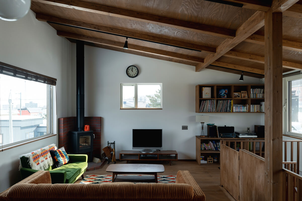 Kさん念願の薪ストーブを設置したリビングは、窓が3方に設けられていてとても明るい。冬はテレビ台の上の窓からまっすぐに朝陽が射し込む。オーディオ収納はKさんが所有するレコードや機器に合わせて造作したもの