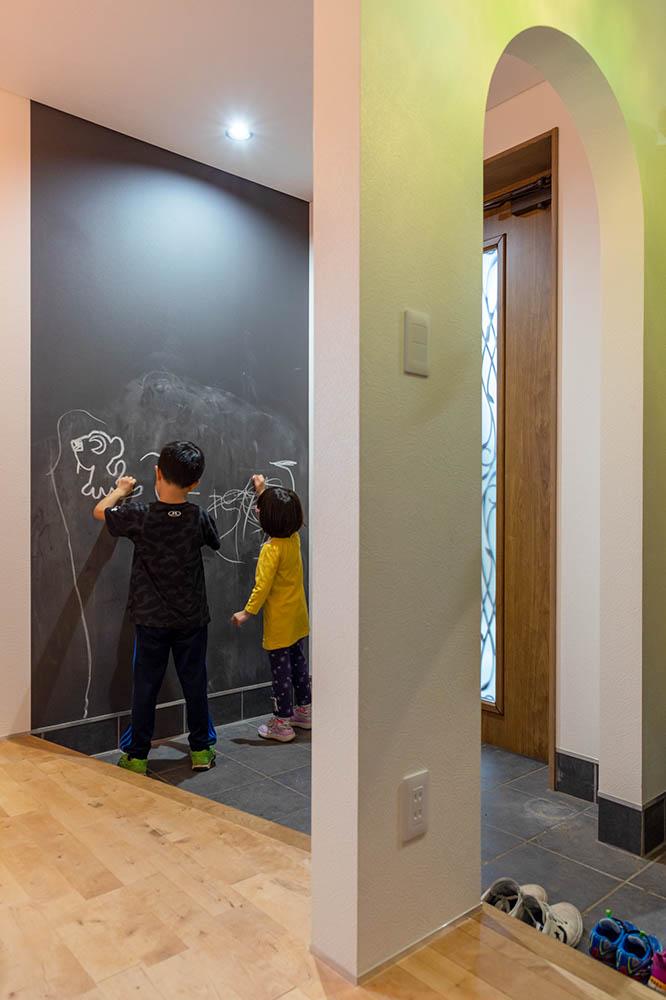 シューズクロークを備えた広々とした玄関の壁は、子どもたちがお絵描きを楽しめるように黒板塗料で仕上げられている