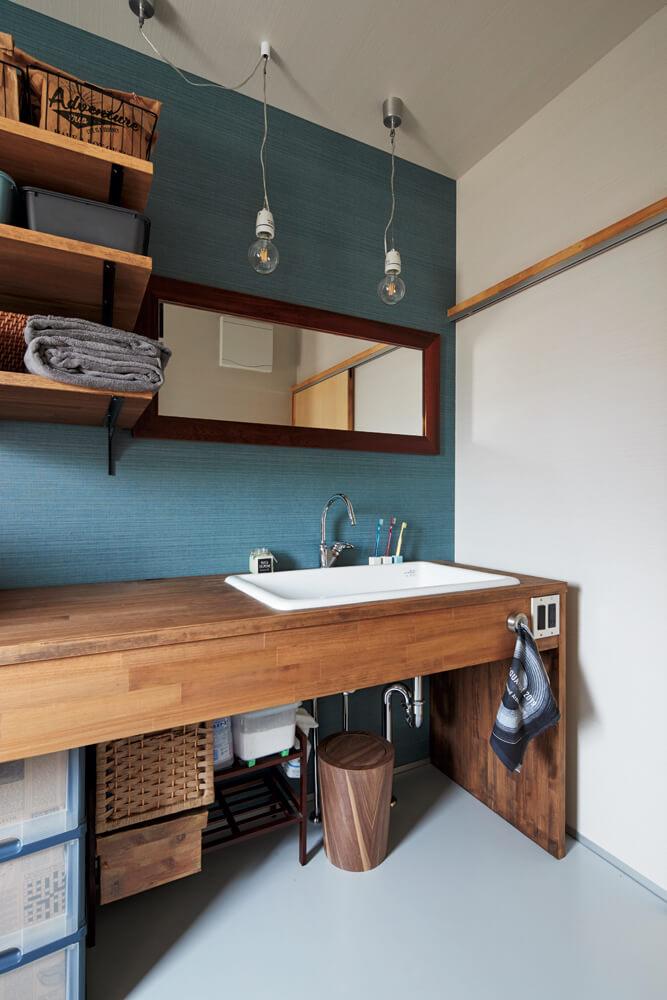 シンプルなデザインで仕上げた造作の木製洗面台。ブルーグリーンのアクセント壁と裸電球のペンダントライトの組み合わせにSさんご夫妻の好みが感じられる