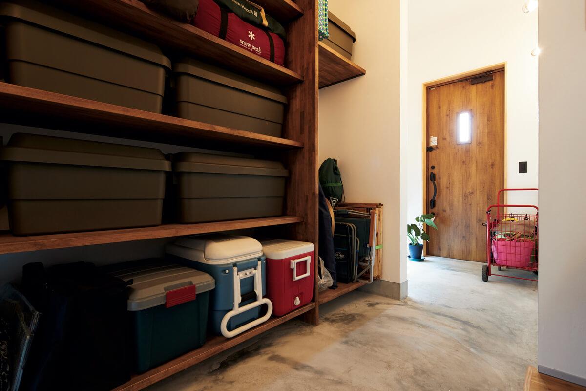 ご夫婦たっての希望で設けられた広い玄関土間。棚にはキャンプ用品などのアウトドアグッズを収納