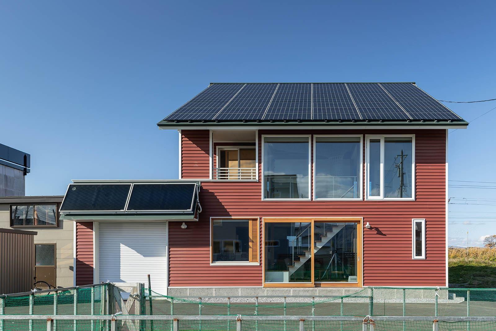 太陽光発電パネルを設置した、大きな開口を持つ片流れ屋根の家。1・2階の大きな開口部と吹き抜けのおかげで室内はいつでも明るい