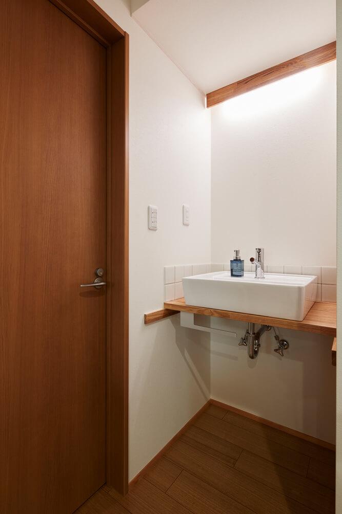 2階ホールの洗面台は壁面にタイルを採用し、スタイリッシュさと機能性を高めた