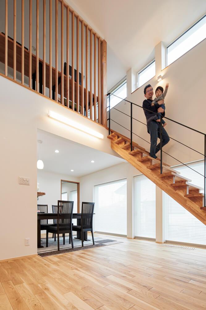 南面の窓から陽射しがたっぷり降り注ぐ開放的なリビング。階段のアイアンの手すりが空間を引き締める