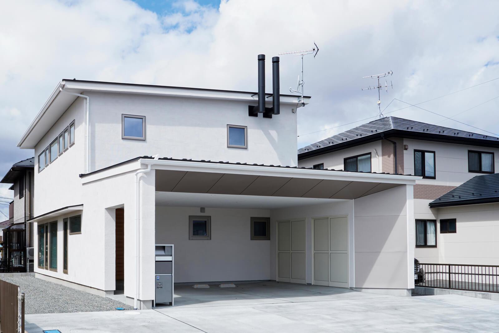 塗り壁仕上げの白い外観が清潔な印象。屋根の上には太陽光発電パネルも搭載している。パッシブ換気によって汚れた空気は排気口を通り、2本の煙突から屋外へと排出される