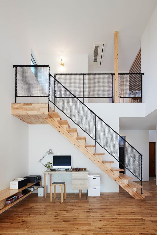 直階段の下にインテリアのデザインに合うデスクを配置。移動しやすく機能的
