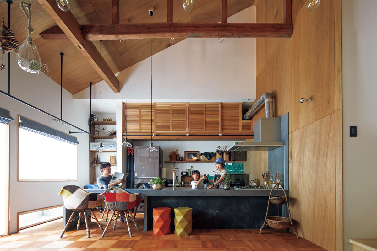 明るく開放感のあるダイニング・キッチン。キッチンは椅子に座る家族と目線が合うよう、床面を一段低く設定。背面収納もたっぷり設けた。デコリエ仕上げのストレートダイニングやアイアンの物干し、ラワン合板仕上げの壁にインダストリアルが香る