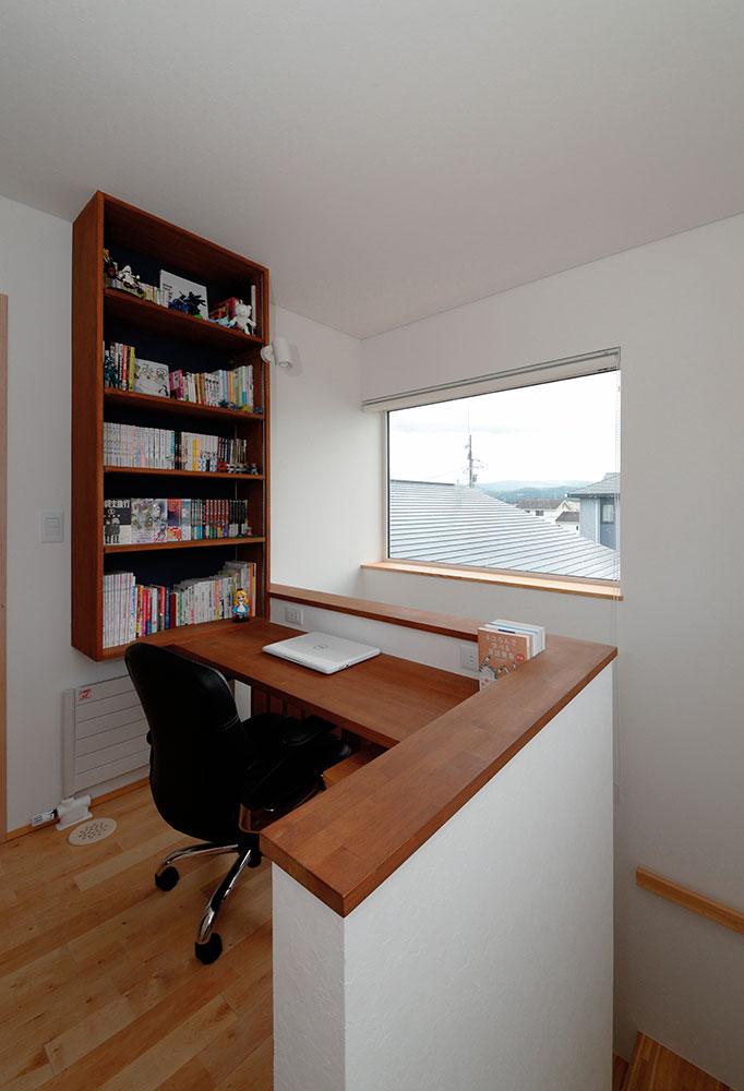 階段を上がってすぐのちょっとしたスペースを活用して書棚とカウンターを造作。視線を上げると窓の向こうの風景が見えて、いい気分転換に