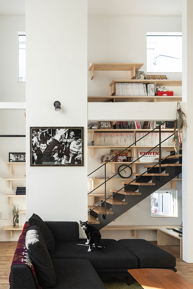 直階段沿いの壁に棚をたくさん造り付けたお住まい