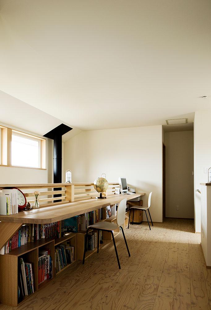 吹き抜けに沿って長いカウンターを造作したお住まい。カウンター下が書棚になっていて、使い勝手も◎