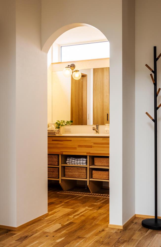 アールの下がり壁の向こうに洗面化粧台とトイレ。レイアウト次第で帰宅後の手洗い・うがい、日常の洗顔・歯磨き、トイレ後の手洗いのすべてがここ1ヵ所で完結