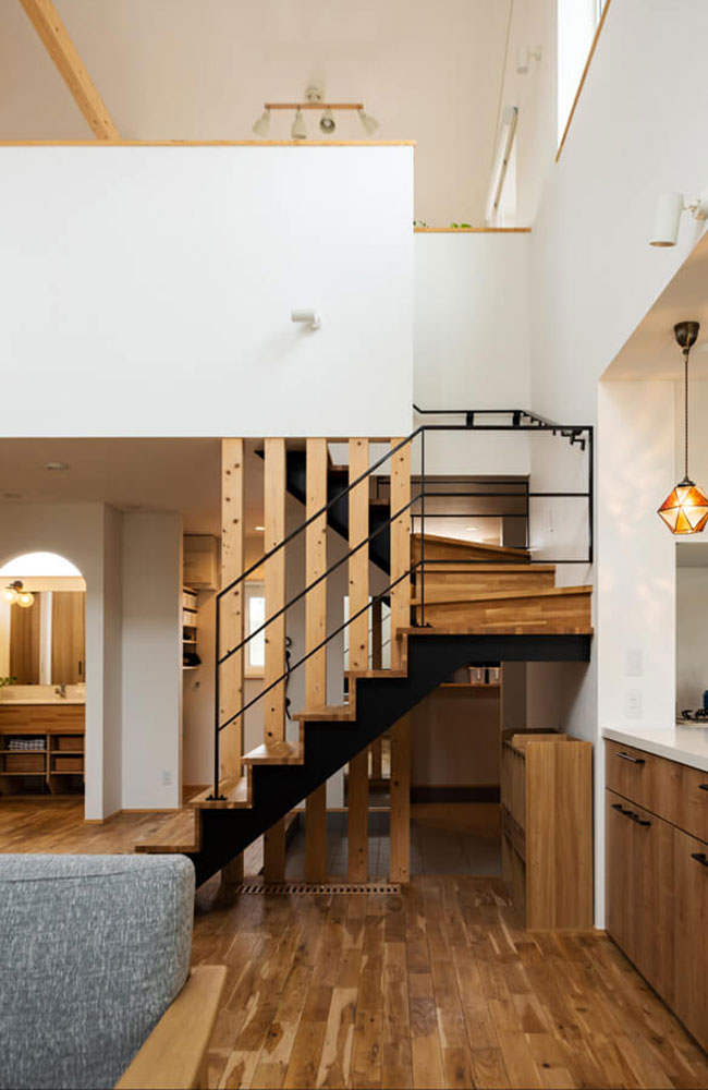 玄関土間から階段下をくぐってLDKへいくこともできるおもしろい間取り。写真左のアールの開口の奥が洗面化粧台