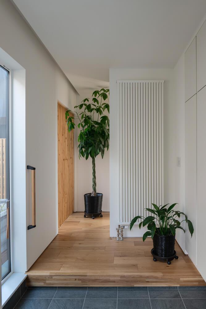 観葉植物が映えるシンプルですっきりとした玄関ホール