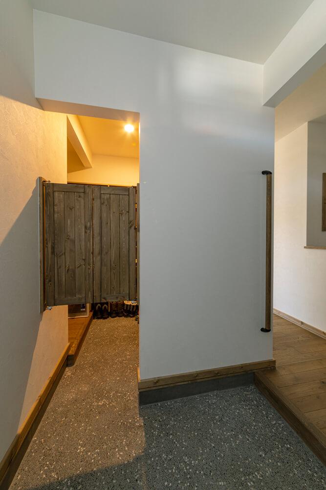 玄関ドアを開けると目に入るのは、シューズルームの目隠しとしてつくった造作のスウィングドア。LDKへは2方向からアクセスできる