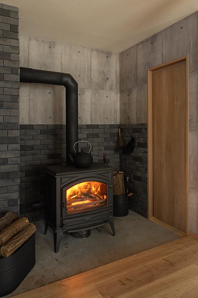 この家の薪ストーブまわりは、グレー色のシックなレンガ調タイルとコンクリートを組み合わせた仕上げ
