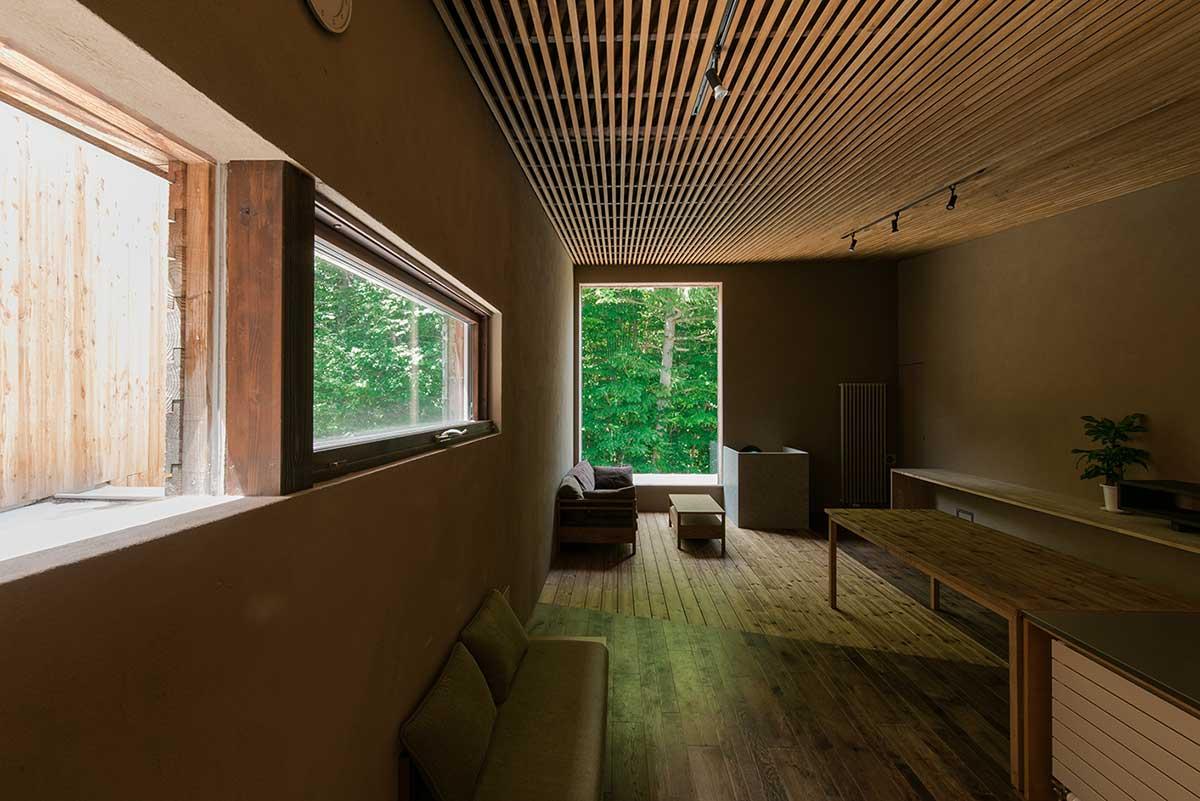 建築地の向かいにあった唐松の林を住まいの一部としてとり込んで設計された家。正面の大きな窓のほか、側面の横長の窓も唐松の林を切り取ってみせる