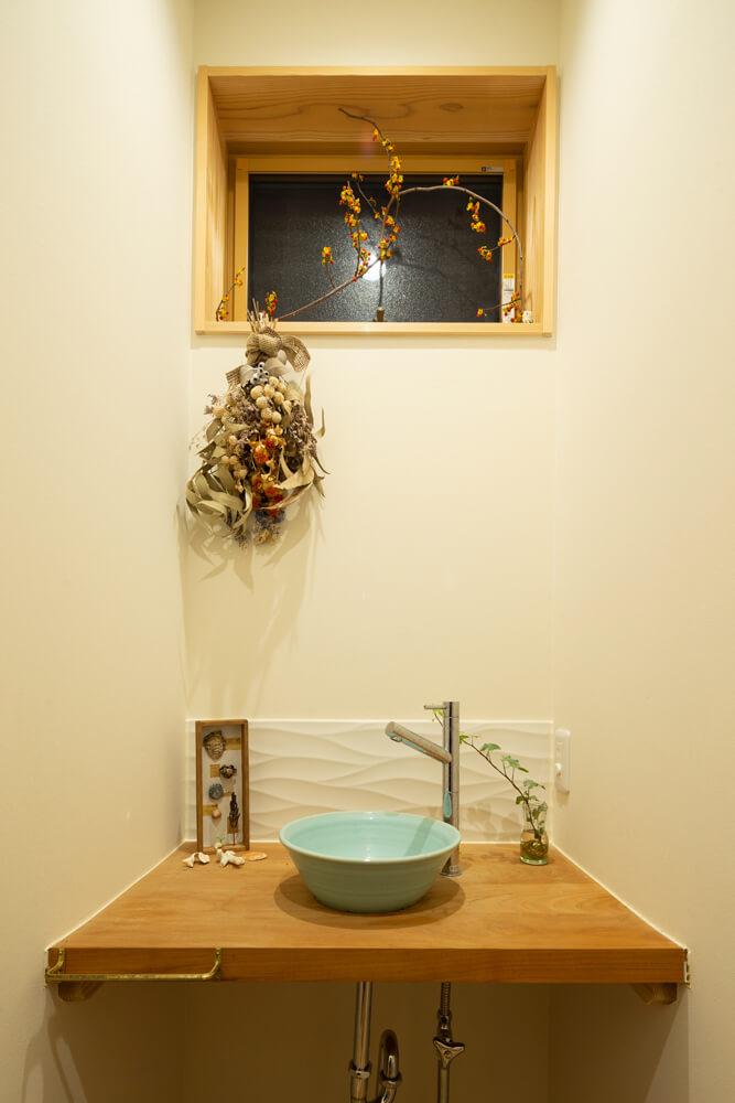 異なる樹種を張った壁の裏手に手洗いスペース。洗面ボウルはお気に入りの作家さんの手によるもの