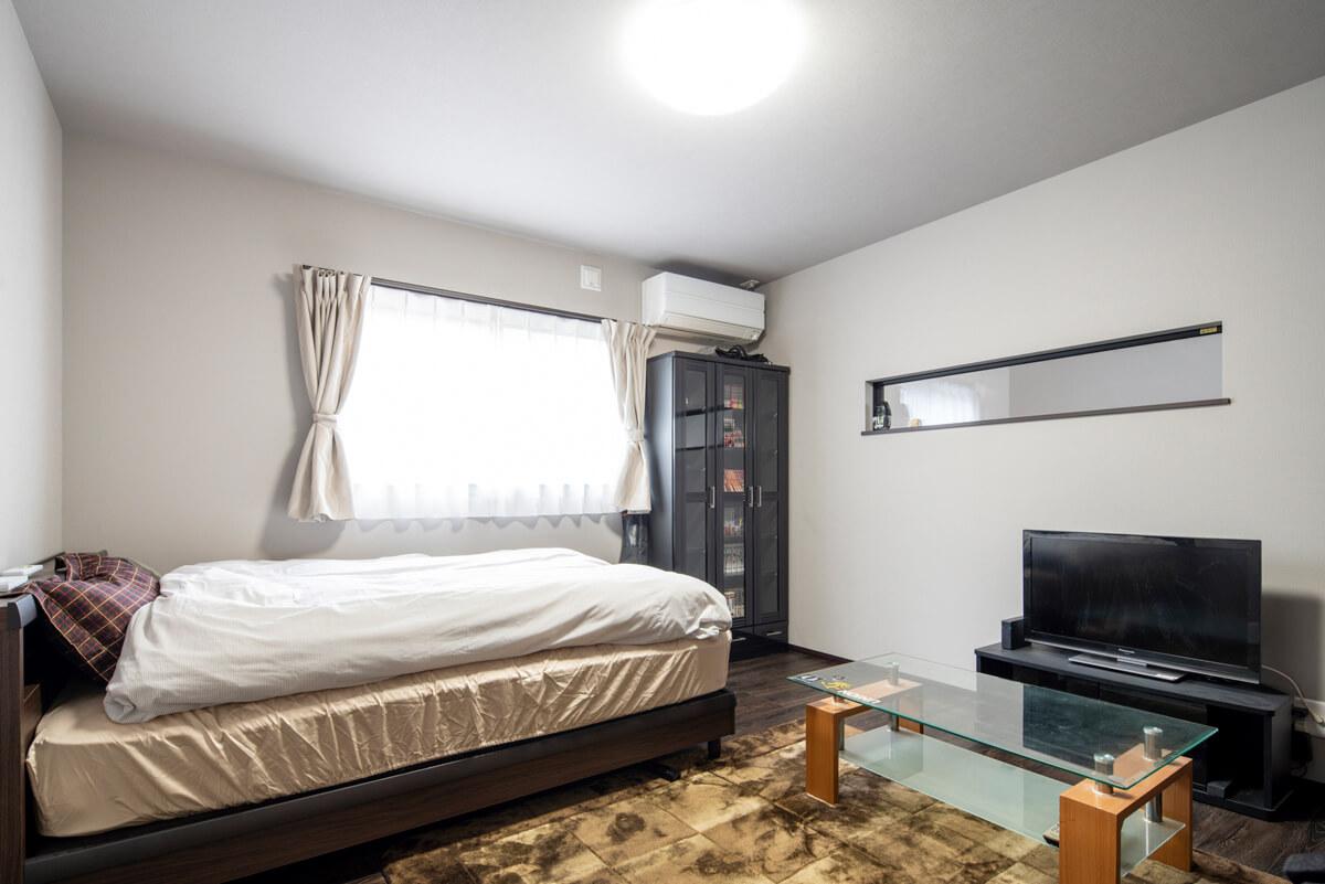 寝室は、グレートーンの色調に。採光や通風のための窓に加え、ガレージ側の壁に横長のFIX窓を設けた