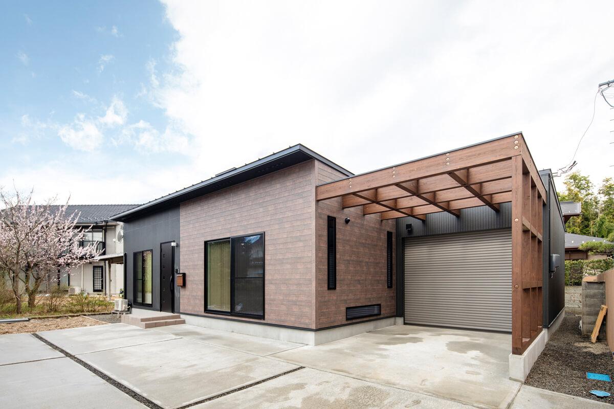 屋根はガルバリウム鋼の板立ハゼ葺き、外壁はブラックとブラウンの窯業系サイディング。玄関ドアやサッシもブラックで統一し、全体が引き締まった印象に。