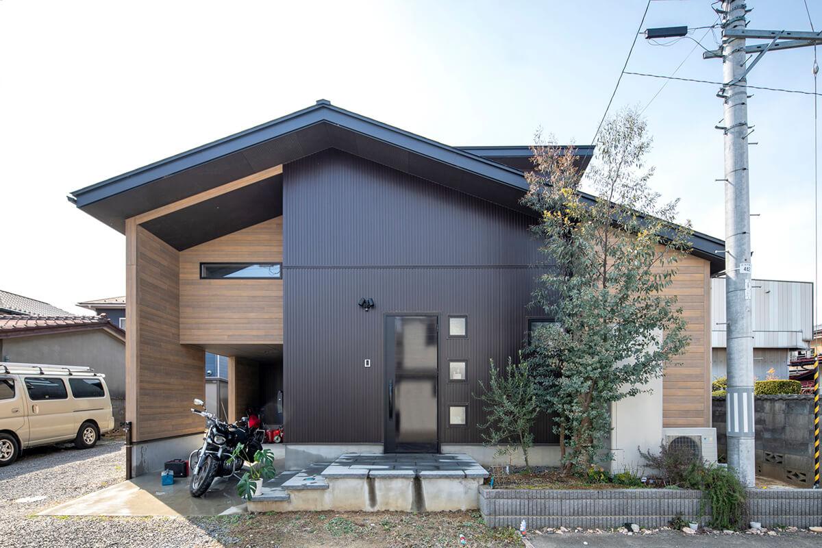「倉庫のような大きい家」という要望を汲んでデザインされたSさんの家は、濃茶のガルバリウム鋼板に木目調サイディングを組み合せたスタイリッシュな印象