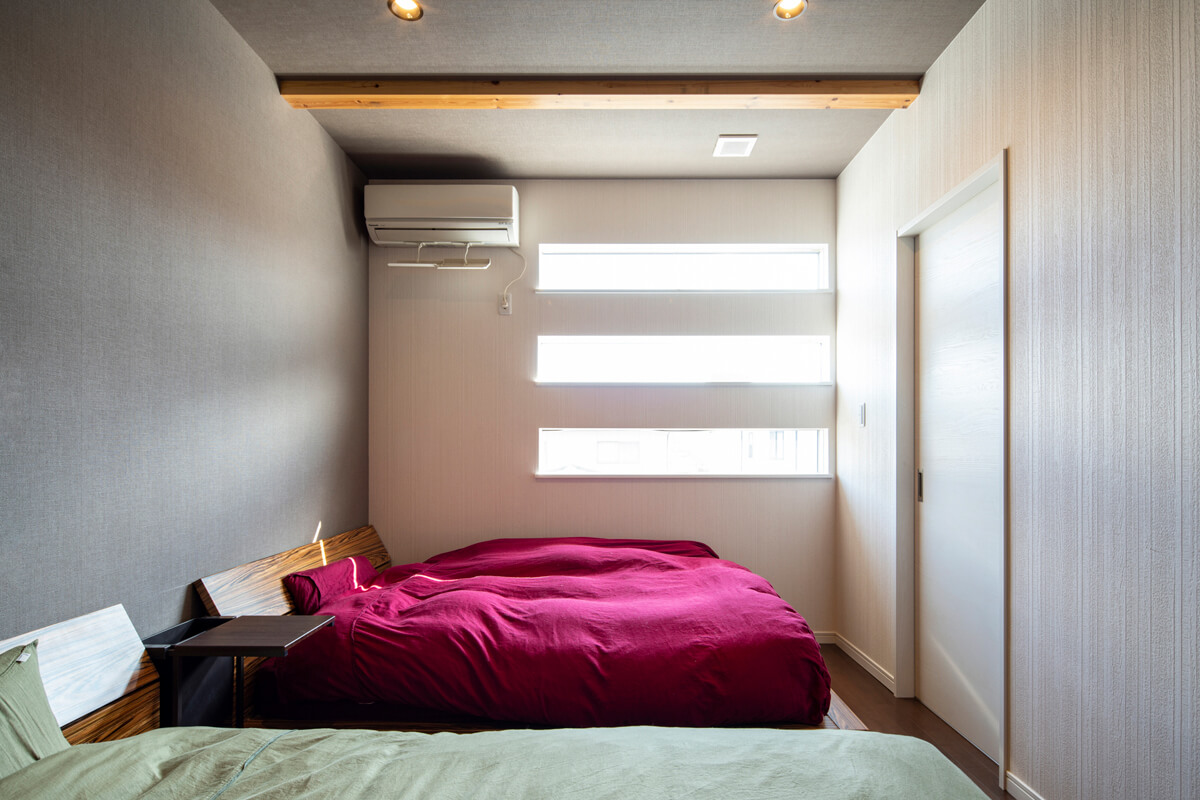 横長の3連窓が個性的な寝室。ご夫妻それぞれに専用のクローゼットを設けている