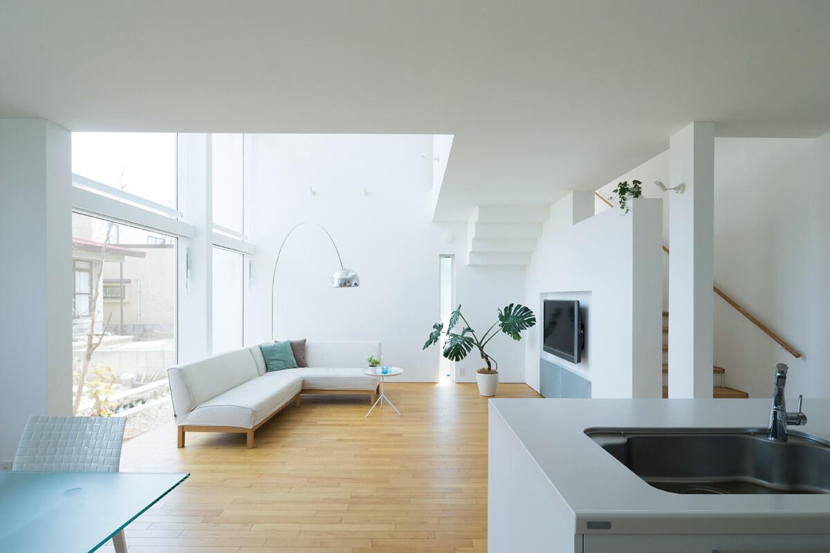 キッチンからリビング方向を見る。余計な装飾のない、白を基調とした伸びやかな空間
