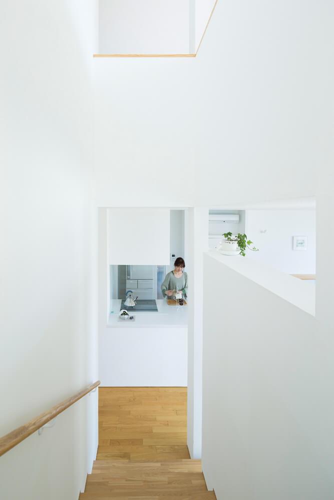 階段室からはキッチンの様子が見られ、スリット越しにリビング(右側)の気配も伝わってくる
