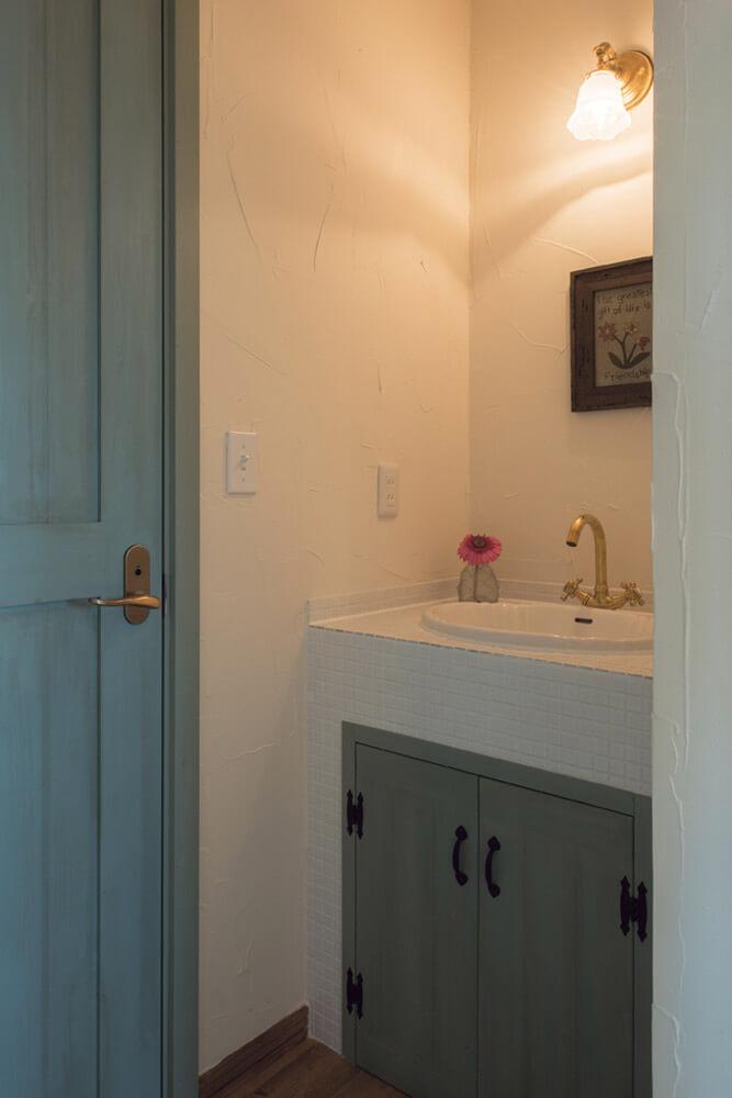 ブルーをアクセントカラーに用いたトイレと造作手洗い。造作の建具や端正な左官仕事で、クラシックな趣に仕上げた