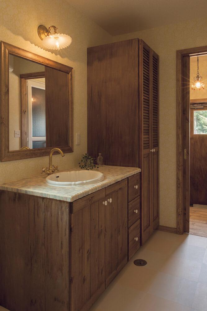 作業着で出入りする裏玄関は、ユーティリティやバスルームと1本の動線で結ばれている。水まわりには木の温もりを生かした造作の収納と洗面台を採用し、機能性と美しさの両立を図った