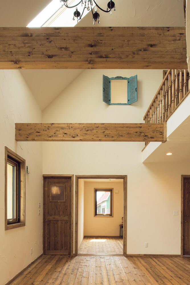 針葉樹の集成材を用いたダイナミックな梁や2階子ども室に設けられたブルーの小窓が、吹き抜けのあるリビングのアクセントに。正面の個室は、予備室