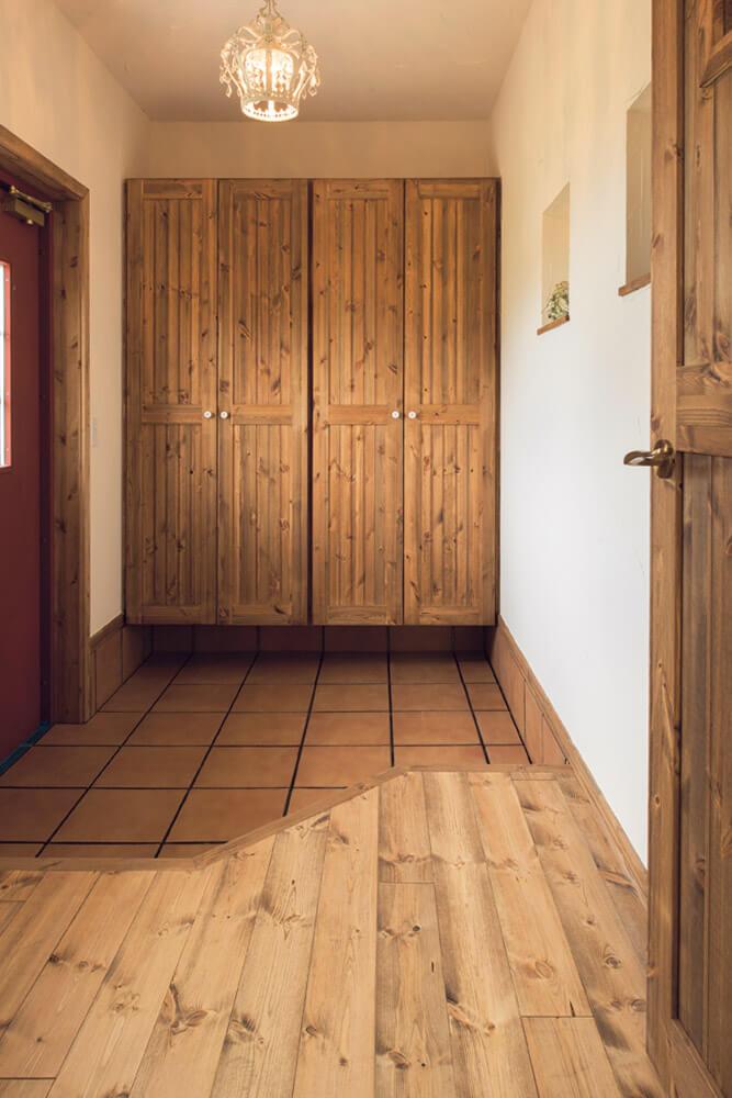 パイン材とテラコッタタイル、塗り壁が温かな空気感を醸し出す玄関。玄関ホールの間仕切りドアを開けると、リビングにつながっている