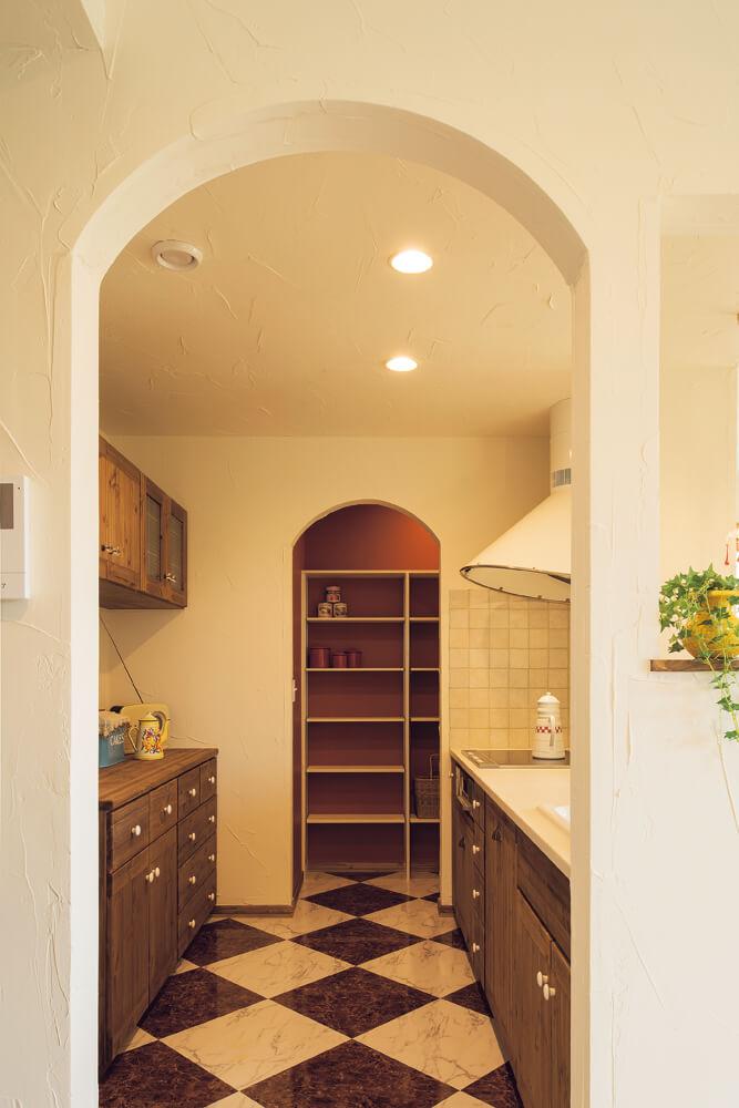 欧州テイストの雑貨が大好きな奥さんお気に入りの造作対面式キッチン。パントリーの壁紙や照明ペンダントに鮮やかな赤を用いて、刺し色に。キッチンのシンクには、歳月が重なるほどに味わいを増す真鍮の水栓金具を取り付けた