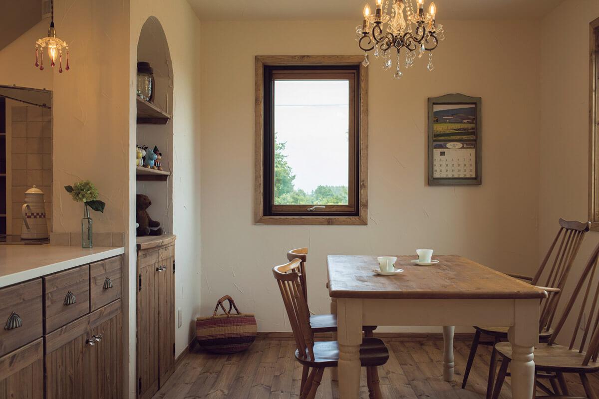 対面式キッチンのダイニング側と隣接する壁には造作収納をしつらえた。奥さんは外の景色を眺めながら家事ができる