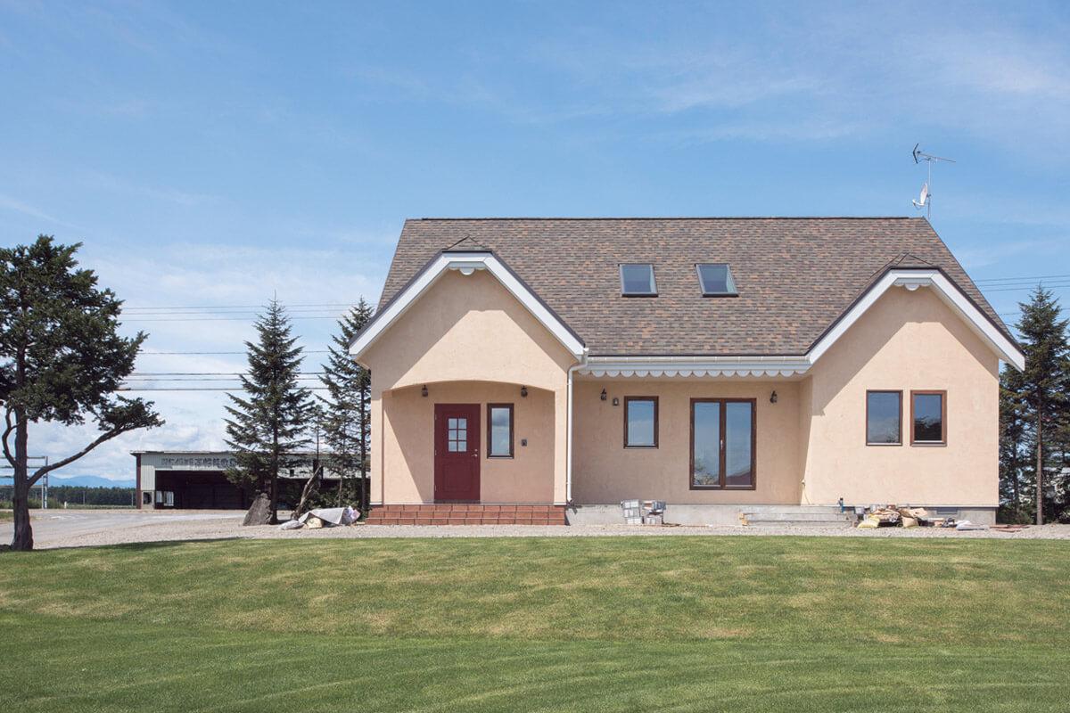 アスファルトシングル葺きの三角屋根、温かな色合いの塗り壁が目を引くIさん宅の外観。家の完成に合わせ「外観のかわいらしさがより引き立つように」と、お父さんが前庭に芝を張ってくれたそう