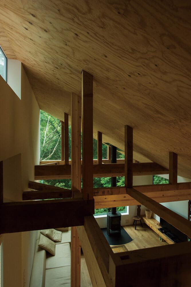 現しにした梁や柱が、外の風景を取り込んで家の中にも森をつくる
