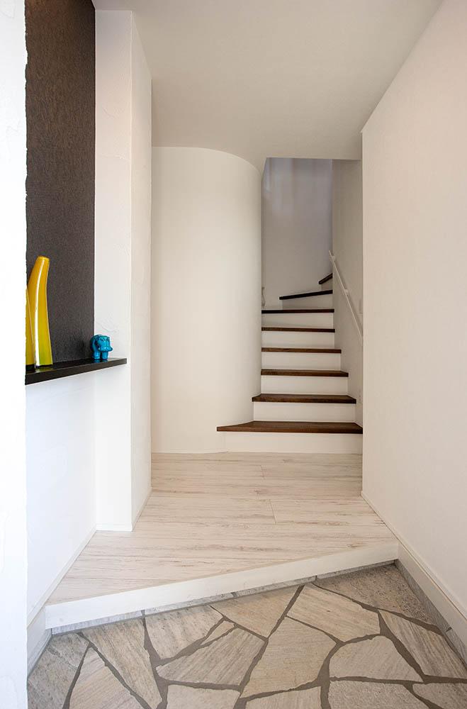 玄関ポーチの正面に2階リビングに続く階段を。1階には家族の寝室やトイレなどを集約した