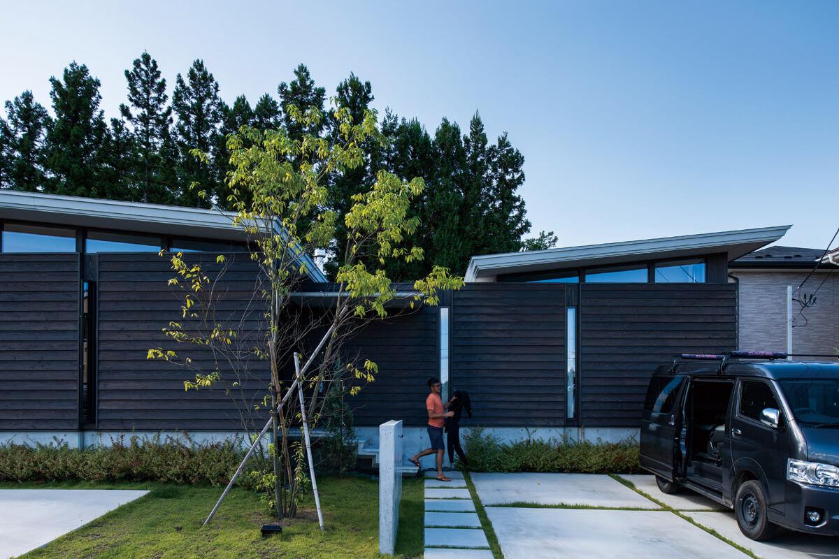 道路側はスギ無垢下見板張りの壁面、反対側は大開口の開放感あふれるつくり。室内への期待感が高まる巧みな設計プラン