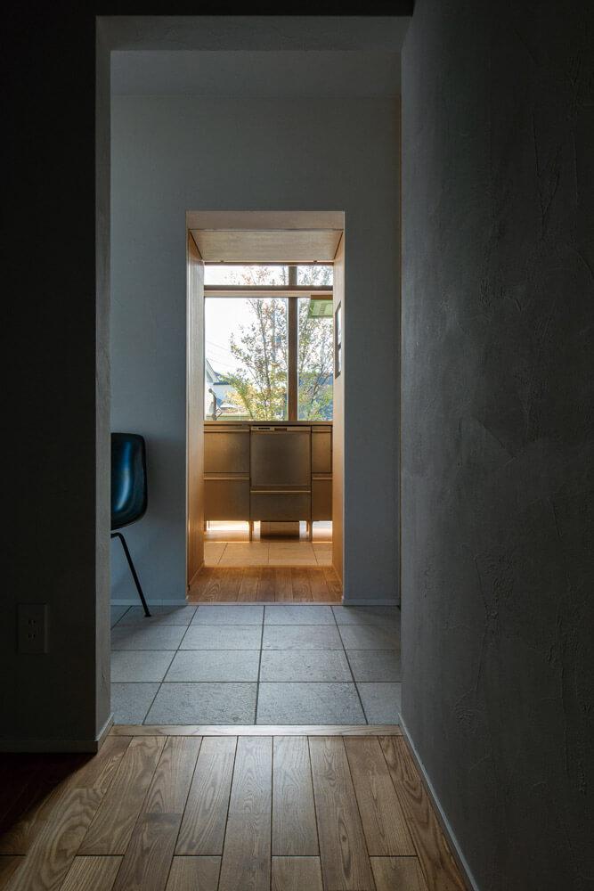 廊下から見たキッチン、その奥には庭が広がる。廊下とキッチンの間は引き戸に