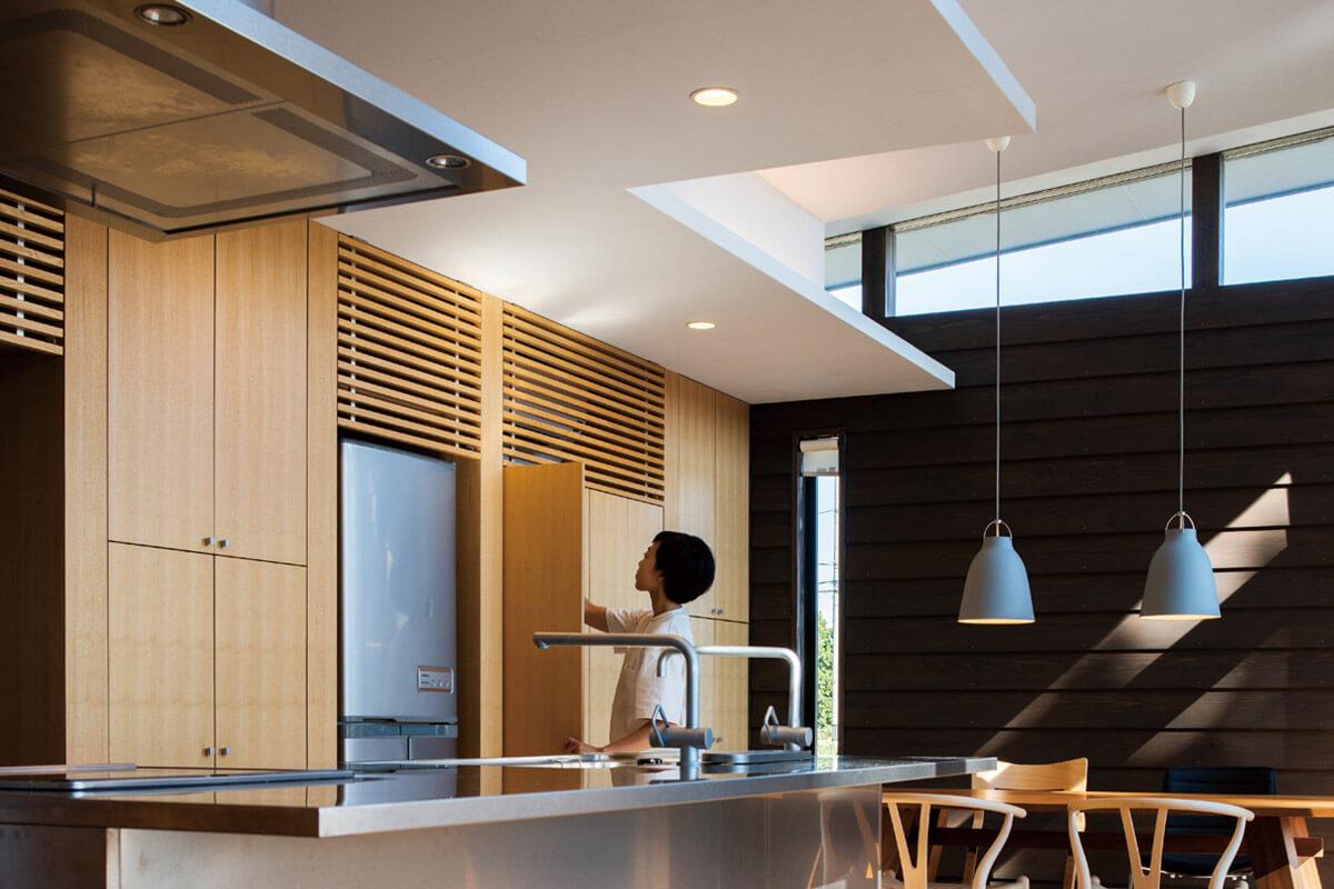 キッチンの壁面には造作の収納スペースを設けた。エアコンもさりげなくカバー