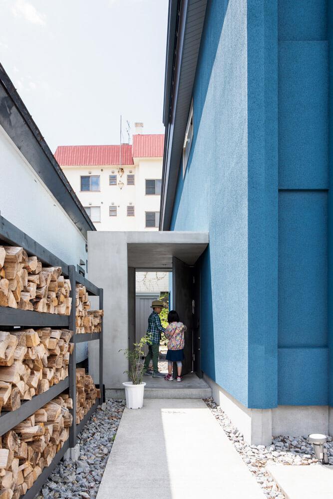 薪棚のあるアプローチを通り、室内へ。アトリエも住まいも、玄関は一つ