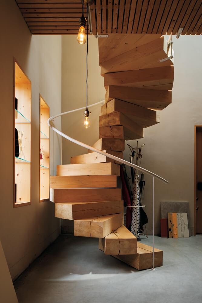 踏板と蹴上げを折紙のように曲げて仕上げた鉄製の螺旋階段。「天窓から螺旋階段を抜けて降りる光が美しいんです」とNさん